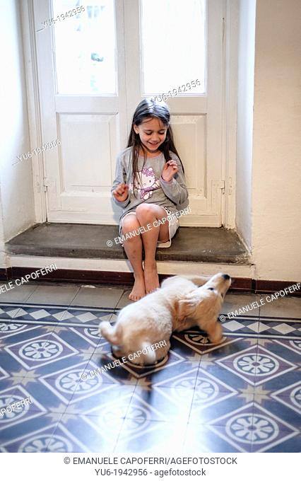 Golden Retriever puppy and little girl at the window of the living room are exchanging caresses