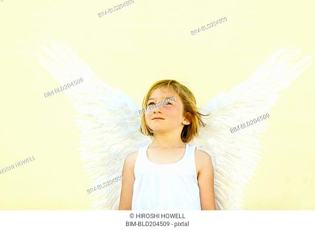 Smiling girl wearing angel wings
