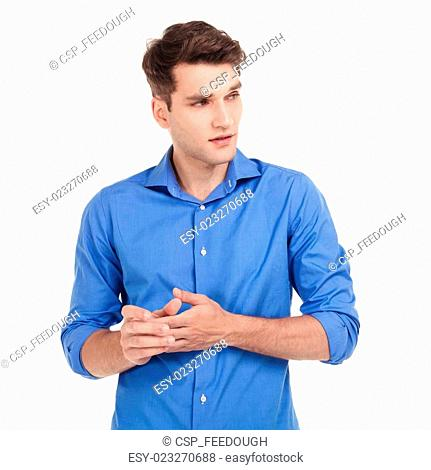Worried young man holding his hands together