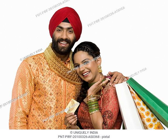 Sikh couple holding shopping bags and credit card