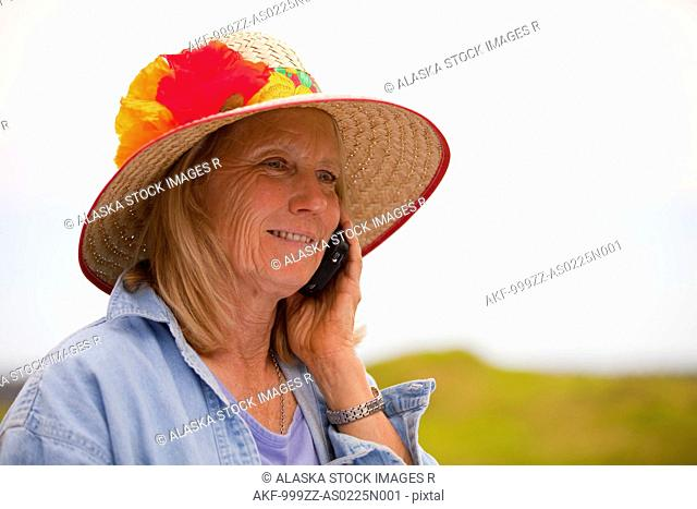 Portrait of mature woman in a flower-decorated garden hat talking on cell phone, Kodiak Island, Southwest Alaska, Summer