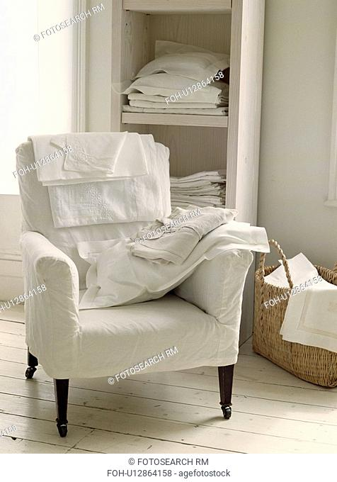 Linen sheets and pillow on armchair with white loosecover