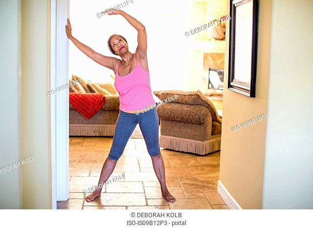 Woman with arms raised doing stretching exercise
