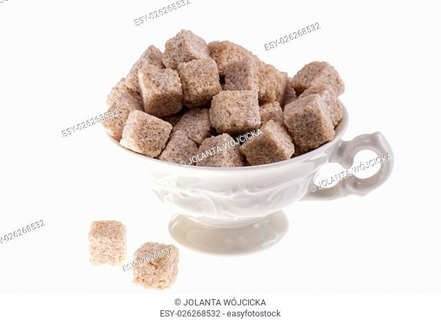 some cane sugar cubes in a small cup on white background