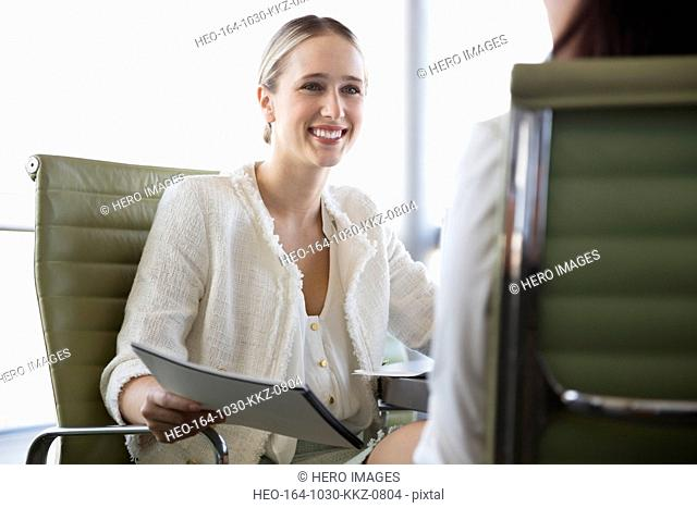 Young businesswoman with file looking at colleague