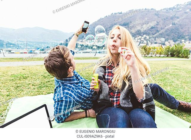 Young couple on picnic blanket blowing and photographing bubbles, Lake Como, Italy