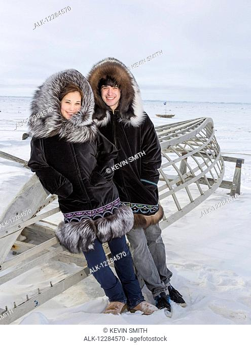 Male and female native youths wear traditional fur parkas while standing next to a boat frame, Barrow, North Slope, Arctic Alaska, USA, Winter