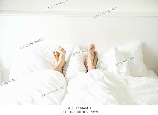 A couple lying in a bed with their feet sticking out from underneath the covers