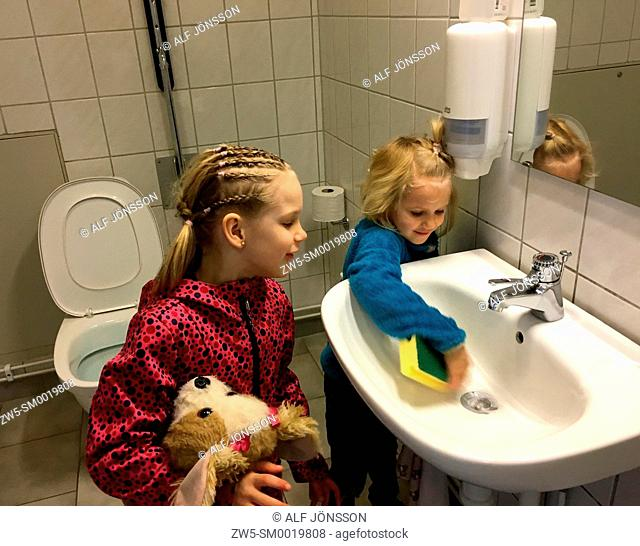 Two little girls, 5 and 7 years old, clean a bathroom in Ystad, Sweden