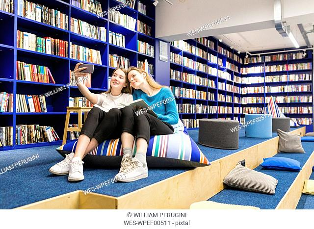 Two teenage girls sitting on beanbag in a public library taking selfie with smartphone