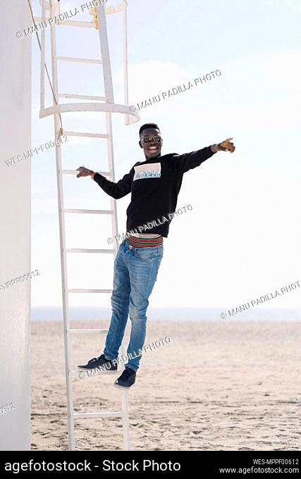 Stylish young man standing on ladder at the beach