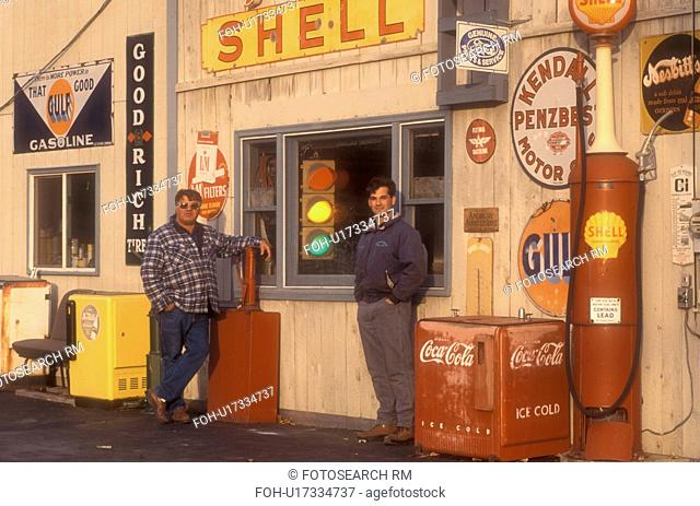 antique, gas station, collectibles, Father and son stand in front of a collection of old signs and other memorabilia on Steve Morris Garage and Auto Sales in...
