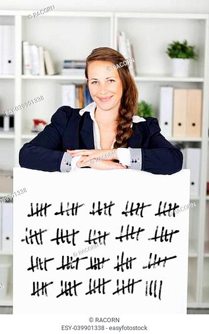 Smiling young business woman with her arms resting on a tally card counting in batches of five struck through with a line