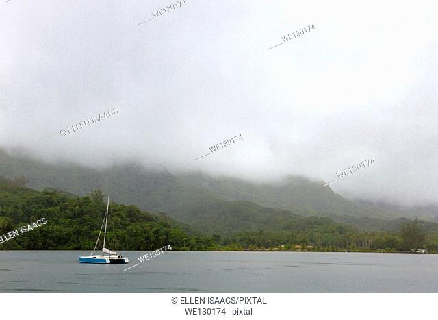 Fog lifting over pretty tropical bay with sailboat anchored in French Polynesia