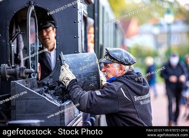 17 October 2020, Mecklenburg-Western Pomerania, Klütz: Peter Bauchwitz of the Parkeisenbahn Wuhlheide association in Berlin fills up the 102-year-old brigade...