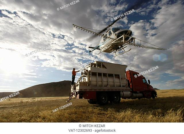 Chemical Spraying Helicopter Flies Over Chemical Storage Truck