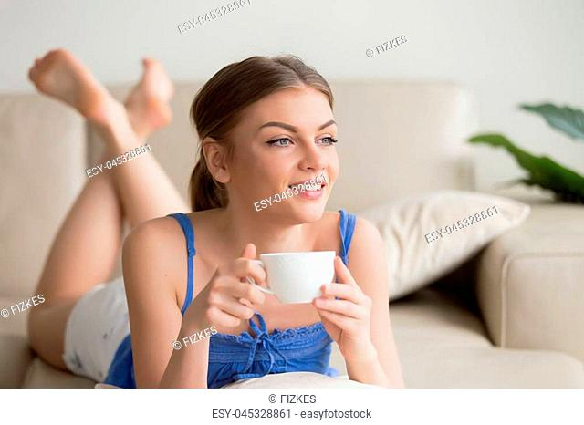 Dreamy young thoughtful woman relaxing on comfortable sofa at home, enjoying cup of coffee in the morning, happy relaxed girl resting on cozy couch