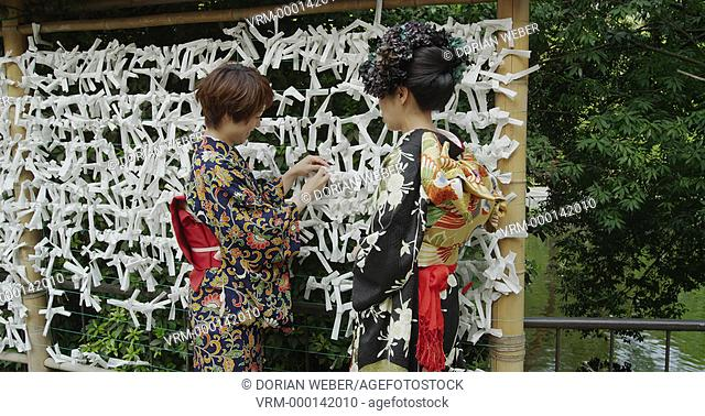 2 Japanese Women in Kimono with o-mikuji paper strips in a Shrine