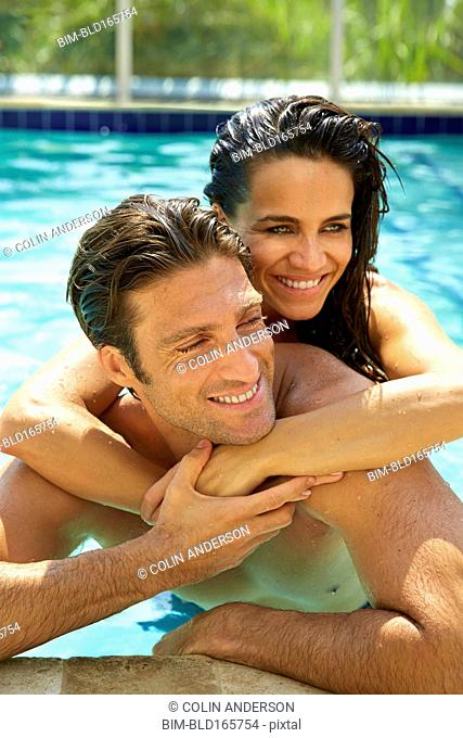 Hispanic couple hugging in swimming pool