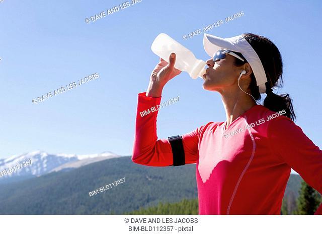 Hispanic runner drinking water in rural landscape