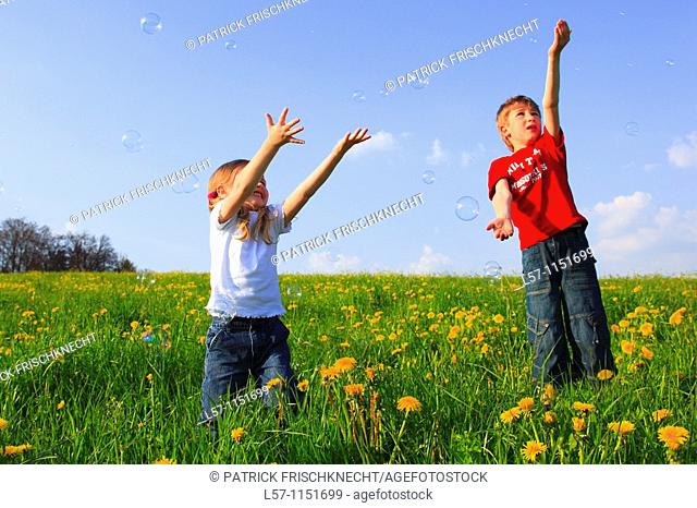 boy and girl playing with bubbles in field of Dandelions,Zuercher Oberland, Zuerich, Switzerland