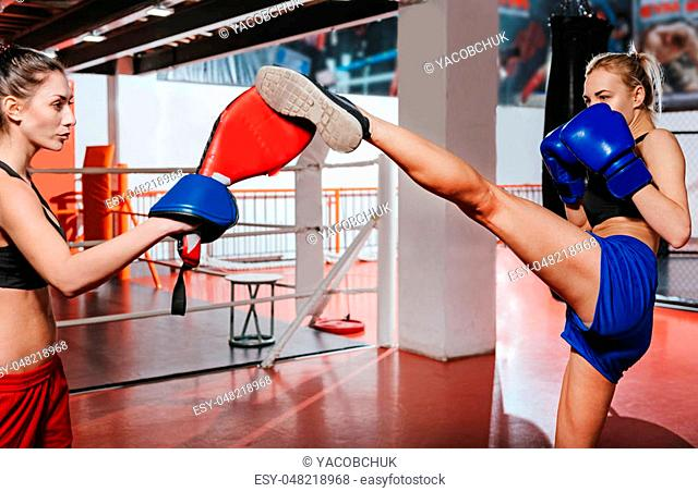 Kick it higher. Brunette pretty woman helping her blonde young friend to master her high leg kick while using special equipment