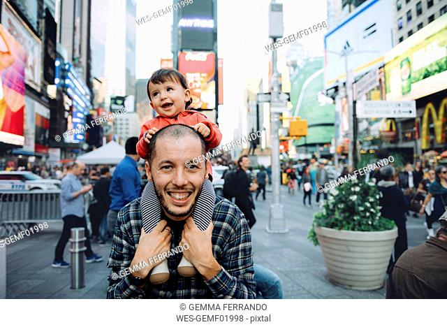 USA, New York, New York City, Times Square, Father with baby on shoulders