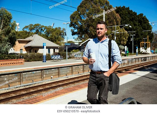 A front-view shot of a mid-adult caucasian businessman walking down a railroad station platform with a cup of coffee in his hand, he is catching the train