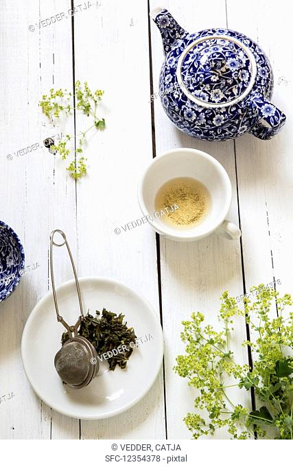 Still life with a blue and white teapot, an empty tea cup, and a tea strainer