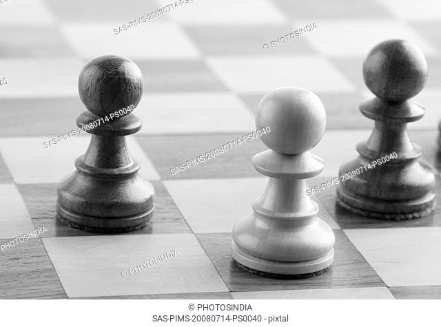 White chess pawn near two black chess pawns on a chess board