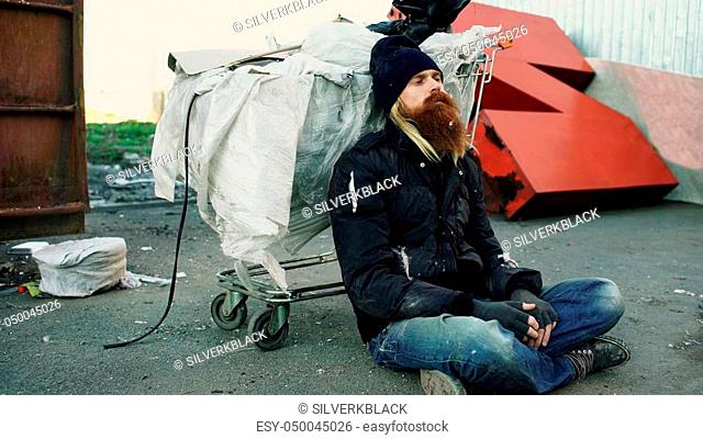 young bearded homeless man sitting on a sidewalk near shopping cart ang garbage container during a cold winter day