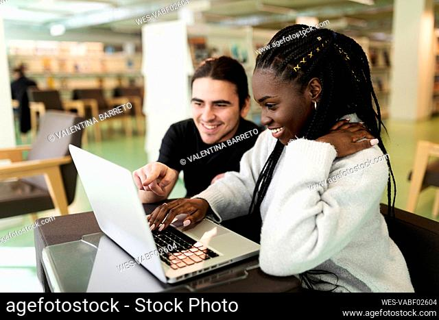 Two smiling students using laptop in a library