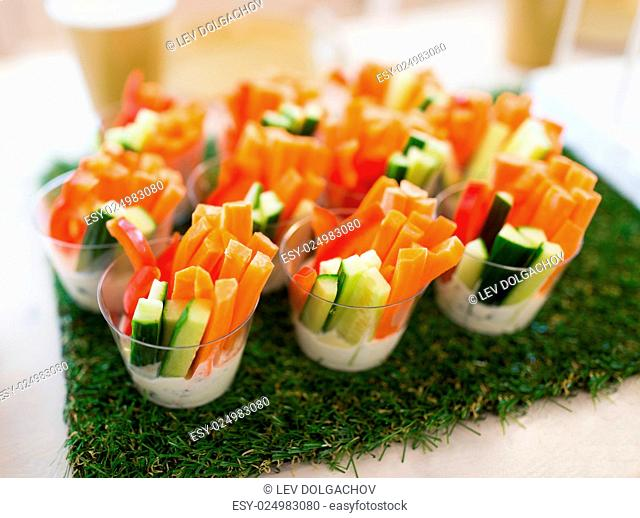 healthy eating, vegetarian food, diet and culinary concept - close up of vegetable snacks on table decorated with artificial grass
