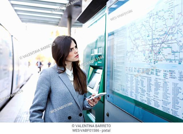 Spain, Barcelona, young woman with smartphone looking at map at station