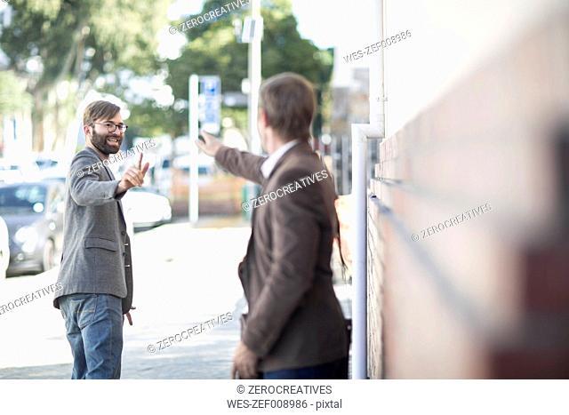 Two men saying goodbye in city