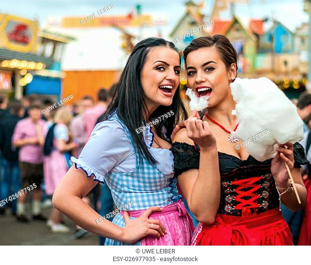 Two young women in traditional Bavarian clothes, dirndl or tracht, laughing with cotton candy floss at the Oktoberfest