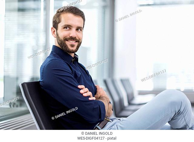 Smiling young businessman sitting in waiting area