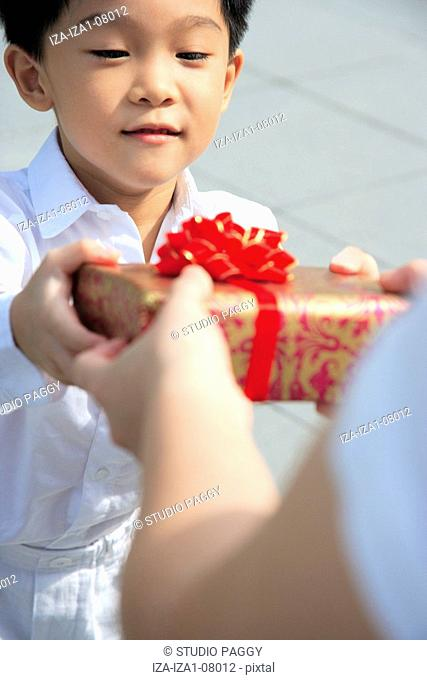 Mid adult woman giving a gift to her son