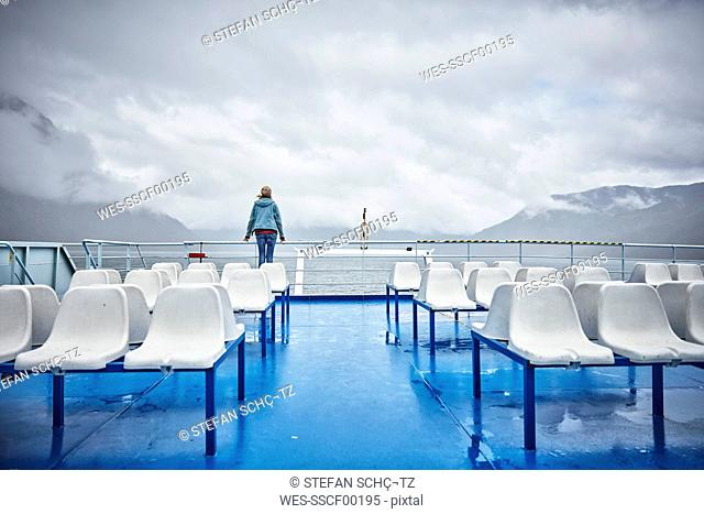 Chile, Hornopiren, woman standing at rail of a ferry looking at fjord