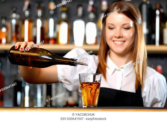 Portrait of a pretty bartender standing smiling and pouring a drink from a bottle, shelves full of bottles with alcohol on the background