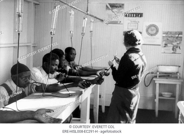 A group of African American men receiving intravenous treatment in a Georgia venereal disease clinic. ca. 1937. During the same decade as the infamous 'Tuskegee...
