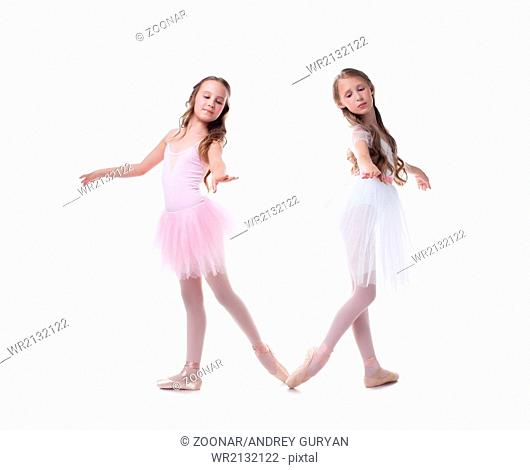 Cute sisters-ballerinas isolated on white backdrop