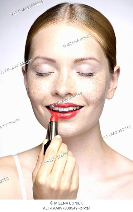 Young woman putting on lipstick