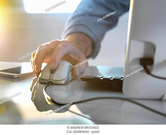 Businessman's hand on a computer mouse working in office