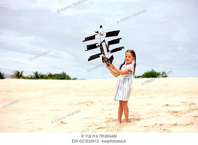 Cute little girl playing on the beach flying ship kite. Child enjoying summer family vacation at the sea