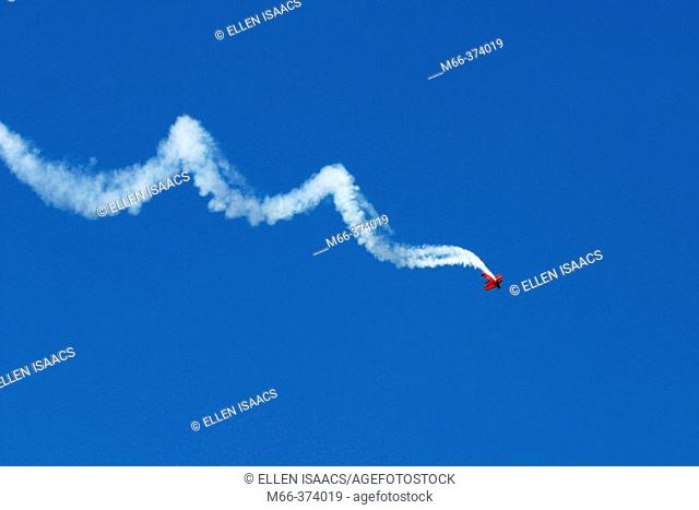 Stunt plane spiraling across the deep blue sky in an air show