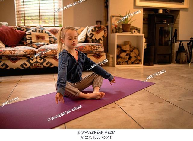 Girl performing yoga in living room