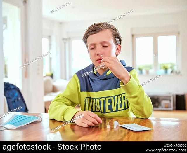 Boy with eyes closed inserting nasal swab for corona rapid test at home