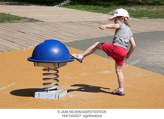 Four Years Old Girl Kicking Swing at Playground