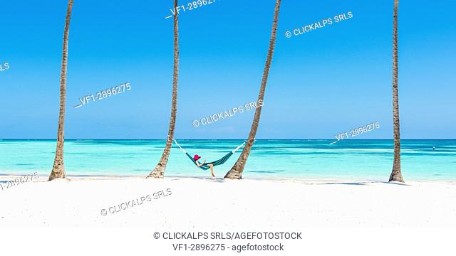 Juanillo Beach (playa Juanillo), Punta Cana, Dominican Republic. Woman relaxing on a hammock on a palm-fringed beach (MR)